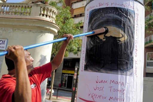 An employee sticks a poster designed by Spanish artist Miquel Barcelo's for Catalonia's final bullfight on September 23, 2011 in Barcelona. Man and bull will dance with death in a Catalan arena for the last time in history on September 25, 2011 before the combat is banned for good from the Spanish region.  AFP PHOTO/ JOSEP LAGO