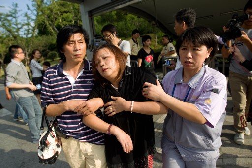 A family member and a rescuer (R) help a female passenger (C) out from the subway station after a train collision in Shanghai on September 27, 2011. A crash between two metro trains in the Chinese city of Shanghai injured more than 40 people, most of them lightly, as more than 500 passengers have been evacuated from the trains after the collision, which was apparently caused by a signal failure.   CHINA OUT      AFP PHOTO