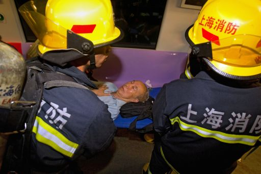 Rescuers attend to an elderly man (C) injured in a subway train collision in Shanghai on September 27, 2011. A crash between two metro trains in the Chinese city of Shanghai injured more than 40 people, most of them lightly, as more than 500 passengers have been evacuated from the trains after the collision, which was apparently caused by a signal failure.     CHINA OUT      AFP PHOTO