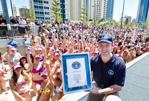 Guinness World Records adjudicator Chris Sheedy holds the certificate awarded to the participants at Surfers Paradise Beach in Gold Coast City on October 2, 2011 after they broke the world record for the longest bikini parade. 357 bikini clad girls paraded on Surfers Paradise beach to break the record of 331 set in 2010 by the Cayman Island Amateur Swimming Association. AFP PHOTO / MURRAY RIX