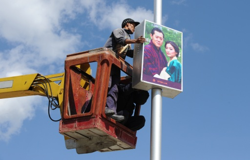 A worker fixes a photograph of the King of Bhutan Jigme Khesar Namgyel Wangchuck and his fiancee Jetsun Pema on a lamp post in Thimphu, Bhutan, on October 12, 2011. Bhutan's king, who will marry on October 13 in a traditional ceremony in the isolated Himalayan nation, is a 31-year-old with a popular touch known to invite his people into his home for tea and a chat. AFP PHOTO/ Prakash SINGH