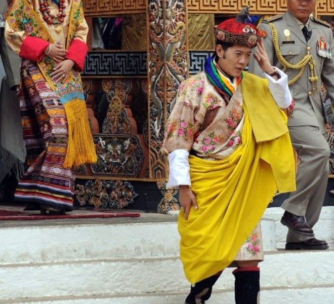 Newly crowned Queen of Bhutan Jetsun Pema (L) and King of Bhutan Jigme Khesar Namgyel Wangchuck (C) walk after their marriage ceremony at the Dzong monastery in Punakha, Bhutan on October 13, 2011. Bhutan's 31-year-old king married a student 10 years his junior in a colourful ceremony showcasing the rich Buddhist culture of one of the world's most remote and insular countries. Amid clouds of incense and chanting monks, the hugely popular King Jigme Khesar Namgyel Wangchuck crowned his queen at the end of a series of rituals in the 17th-century fortified monastery chosen for the occasion. AFP PHOTO/ Prakash SINGH