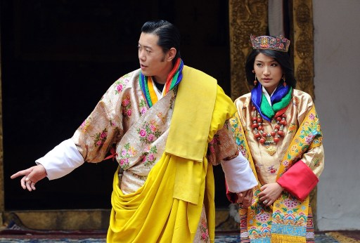 King of Bhutan Jigme Khesar Namgyel Wangchuck (L) and newly crowned Queen of Bhutan Jetsun Pema (R) acknowledge the crowds after their marriage ceremony at the Dzong monastery in Punakha, Bhutan on October 13, 2011. Bhutan's 31-year-old king married a student 10 years his junior in a colourful ceremony showcasing the rich Buddhist culture of one of the world's most remote and insular countries. Amid clouds of incense and chanting monks, the hugely popular King Jigme Khesar Namgyel Wangchuck crowned his queen at the end of a series of rituals in the 17th-century fortified monastery chosen for the occasion. AFP PHOTO/ Prakash SINGH