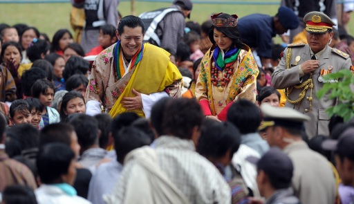 King of Bhutan Jigme Khesar Namgyel Wangchuck (L) and newly crowned Queen of Bhutan Jetsun Pema (R) greet the public after their marriage ceremony at the Dzong monastery in Punakha, Bhutan on October 13, 2011. Bhutan's 31-year-old king married a student 10 years his junior in a colourful ceremony showcasing the rich Buddhist culture of one of the world's most remote and insular countries. Amid clouds of incense and chanting monks, the hugely popular King Jigme Khesar Namgyel Wangchuck crowned his queen at the end of a series of rituals in the 17th-century fortified monastery chosen for the occasion. AFP PHOTO/ Prakash SINGH
