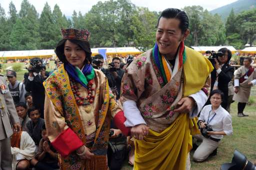 Newly crowned Queen of Bhutan Jetsun Pema (L) and King of Bhutan Jigme Khesar Namgyel Wangchuck (R) acknowledge the crowds after their marriage ceremony at the Dzong monastery in Punakha, Bhutan on October 13, 2011. Bhutan's 31-year-old king married a student 10 years his junior in a colourful ceremony showcasing the rich Buddhist culture of one of the world's most remote and insular countries. Amid clouds of incense and chanting monks, the hugely popular King Jigme Khesar Namgyel Wangchuck crowned his queen at the end of a series of rituals in the 17th-century fortified monastery chosen for the occasion. AFP PHOTO/ Prakash SINGH
