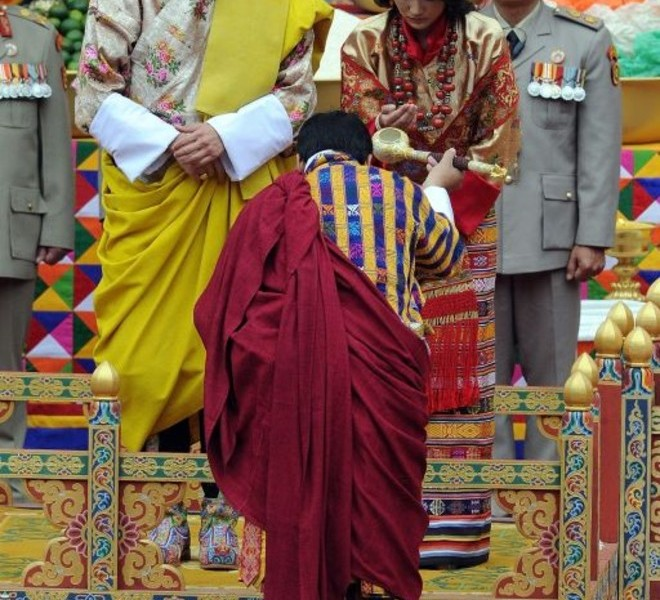 King of Bhutan Jigme Khesar Namgyel Wangchuck (CL) and future queen Jetsun Pema (CR) stand together during their marriage ceremony in the main courtyard of the 17th-century fortified monastery or dzong in Punakha on October 13, 2011. Bhutan's 31-year-old king marries a student 10 years his junior on October 13 in an isolated valley high in the Himalayas where thousands of nomads and villagers have gathered to celebrate.  AFP PHOTO / PRAKASH SINGH