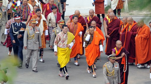 King of Bhutan Jigme Khesar Namgyel Wangchuck (C) arrives with Bhutanese Prime MInister Jigme Y. Thinley (CR, orange) for the king's marriage ceremony to Jetsun Pema (unseen) at the 17th-century fortified monastery or dzong in Punakha on October 13, 2011. Bhutan's 31-year-old king marries a student 10 years his junior on October 13 in an isolated valley high in the Himalayas where thousands of nomads and villagers have gathered to celebrate.  AFP PHOTO / PRAKASH SINGH