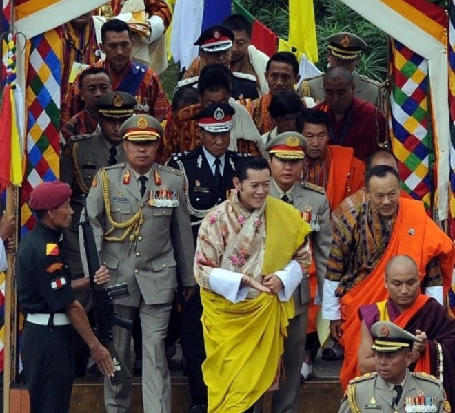King of Bhutan Jigme Khesar Namgyel Wangchuck (C) arrives with Bhutanese Prime MInister Jigme Y. Thinley (R, orange) for the king's marriage ceremony to Jetsun Pema (unseen) at the 17th-century fortified monastery or dzong in Punakha on October 13, 2011. Bhutan's 31-year-old king marries a student 10 years his junior on October 13 in an isolated valley high in the Himalayas where thousands of nomads and villagers have gathered to celebrate.  AFP PHOTO / PRAKASH SINGH