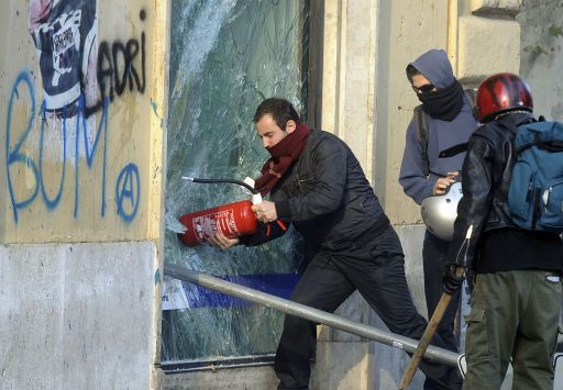 A protester uses an extinguisher to break a window during a demonstration in Rome on October 15, 2011. Protesters set fire to a government building, torched cars and smashed bank windows in Rome in the worst violence of worldwide demonstrations against corporate greed and government cutbacks.Tens of thousands took to the streets of the Italian capital for a march that turned violent and equal numbers rallied in Madrid and Lisbon. Protestors launched worldwide street demonstrations on October 15 against corporate greed and biting cutbacks in a rolling action targetting 951 cities in 82 countries across the planet in Asia, Europe, Africa and the Americas. AFP PHOTO / FILIPPO MONTEFORTE