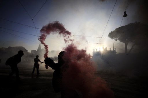 "Protesters use extinguishers towards riot police during a demonstration, in Rome on October 15, 2011. Clashes broke out at an anti-capitalist protest in Rome attended by tens of thousands of people as part of a global day of protests inspired by the ""Occupy Wall Street"" and ""Indignant"" movements, with one group setting fire to a government office and riot police firing tear gas and water. Protestors launched worldwide street demonstrations on October 15 against corporate greed and biting cutbacks in a rolling action targetting 951 cities in 82 countries. AFP PHOTO / FILIPPO MONTEFORTE"