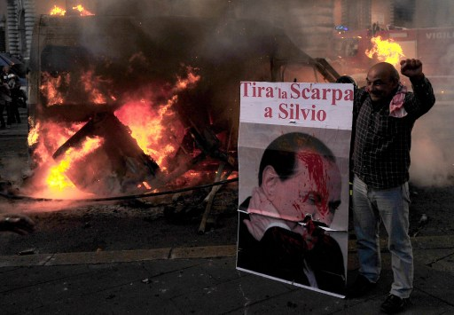 "A demonstrator holds a poster reading ""throw a shoe at Silvio"" during a demonstration, in Rome on October 15, 2011. Tens of thousands marched in Rome today as part of a global day of protests inspired by the ""Occupy Wall Street"" and ""Indignant"" movements, with the Italian capital under a security lockdown. Protesters launched worldwide street demonstrations on October 15 against corporate greed and biting cutbacks in a rolling action targetting 951 cities in 82 countries.     AFP PHOTO/ ALBERTO PIZZOLI"