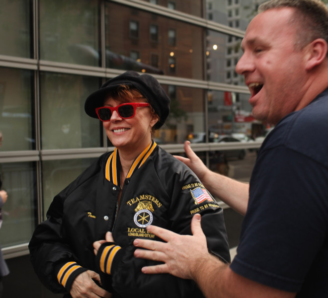 NEW YORK, NY - OCTOBER 18: A Teamster (R) gives his jacket to actress Susan Sarandon at a labor rally where members of the Occupy Wall Street community joined Teamsters in front of the auction house Sotheby's to protest the lockout of union art handlers in a contract dispute on October 18, 2011 in New York City. The activists who make up Occupy Wall Street have been gradually converging on the financial district over the past month to rally against the influence of corporate money in politics among a host of other issues. The protests, which have no stated demands, have spread to other cities and a number of countries over the last week leading to hundreds of arrests as world leaders and police anticipate their next move.  (Photo by Spencer Platt/Getty Images)