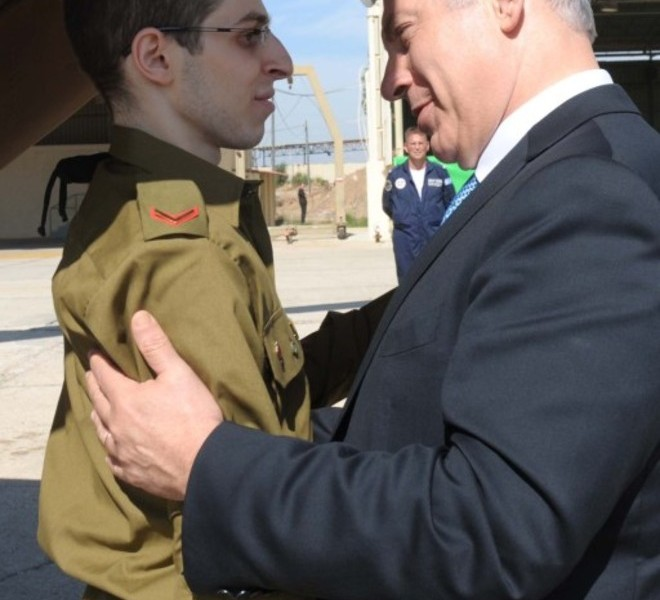 "EDITOR'S NOTE - RESTRICTED TO EDITORIAL USE - MANDATORY CREDIT ""AFP PHOTO/GPO "" - NO MARKETING NO ADVERTISING CAMPAIGNS - DISTRIBUTED AS A SERVICE TO CLIENTS A handout picture released by the Israeli Government Press Office (GPO) shows Israeli soldier Gilad Shalit being welcomed by Israeli Prime Minister Benjamin Netanyahu at the Tel Nof airbase near Tel Aviv on October 18, 2011 following his release following 5 years of Hamas captivity under a landmark Egyptian-mediated deal that will see Israel release a total of 1,027 Palestinian prisoners. AFP PHOTO/GPO/HO"
