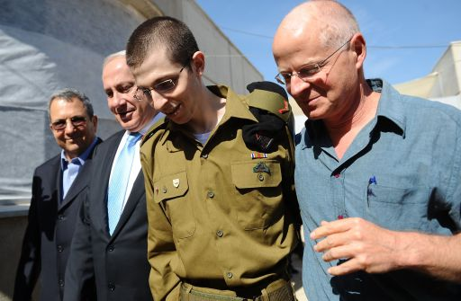 "EDITOR'S NOTE - RESTRICTED TO EDITORIAL USE - MANDATORY CREDIT ""AFP PHOTO/PMO "" - NO MARKETING NO ADVERTISING CAMPAIGNS - DISTRIBUTED AS A SERVICE TO CLIENTS A handout picture released by the Israeli Prime Minister Office shows Israeli soldier Gilad Shalit (C) being hugged by his father Noam (R) for the first time in five years as they walk alongside Israeli Prime Minister Benjamin Netanyahu and Defense Minister Ehud Barak at the Tel Nof airbase near Tel Aviv on October 18, 2011 following his release following 5 years of Hamas captivity under a landmark Egyptian-mediated deal that will see Israel release a total of 1,027 Palestinian prisoners. AFP PHOTO/PMO/HO"