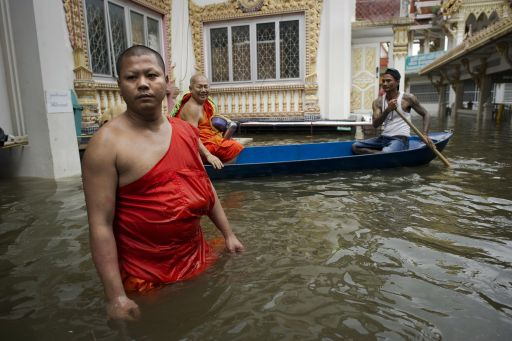 A Buddhist monk wades through floodwaters in a temple in Bang Bua Thon, in Nonthaburi province, suburban Bangkok, on October 18, 2011. The Thai premier said reconstruction from massive floods swamping vast swathes of the country is expected to cost the government over 3.3 billion USD -- a fifth more than previously estimated. TOPSHOTS   AFP PHOTO / Nicolas ASFOURI