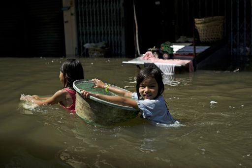A girl holds on to a plastic bowl as she makes her way through floodwaters after a mud and sandbag wall collapsed in Bang Bua Thong in Nonthaburi province, suburban Bangkok, on October 19, 2011. Thailand's premier urged the kingdom's rival political factions on October 19 to work together to tackle the worst floods in decades, as the opposition called on her to declare a state of emergency.     AFP PHOTO/ Nicolas ASFOURI