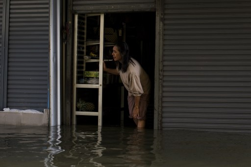A local resident looks out from her shop in floodwaters after a mud and sandbag wall collapsed in Bang Bua Thong, in Nonthaburi province, suburban Bangkok, on October 19, 2011. Thailand's premier urged the kingdom's rival political factions to work together to tackle the worst floods in decades, as the opposition called on her to declare a state of emergency. AFP PHOTO/ Nicolas ASFOURI