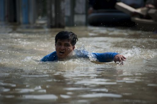 A local resident swims in floodwaters after a mud and sandbag wall collapsed in Bang Bua Thong, in Nonthaburi province, suburban Bangkok, on October 19, 2011. Thailand's premier urged the kingdom's rival political factions to work together to tackle the worst floods in decades, as the opposition called on her to declare a state of emergency. AFP PHOTO/ Nicolas ASFOURI
