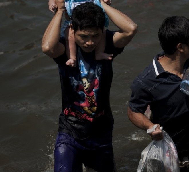 A local resident holds a child as he walks in floodwaters after a mud and sandbag wall collapsed in Bang Bua Thong, in Nonthaburi province, suburban Bangkok, on October 19, 2011. Thailand's premier urged the kingdom's rival political factions to work together to tackle the worst floods in decades, as the opposition called on her to declare a state of emergency. AFP PHOTO/ Nicolas ASFOURI
