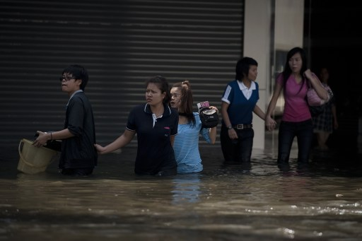 Local residents hold hands as they walk in floodwaters after a mud and sandbag wall collapsed in Bang Bua Thong, in Nonthaburi province, suburban Bangkok, on October 19, 2011. Thailand's premier urged the kingdom's rival political factions Wednesday to work together to tackle the worst floods in decades, as the opposition called on her to declare a state of emergency. AFP PHOTO/ Nicolas ASFOURI