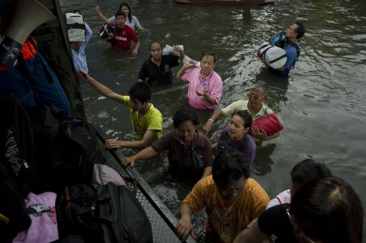 Local residents walk in floodwaters towards an army truck as they leave their homes, after a mud and sandbag wall collapsed in Bang Bua Thong, in Nonthaburi province, suburban Bangkok, on October 19, 2011. Thailand's premier urged the kingdom's rival political factions to work together to tackle the worst floods in decades, as the opposition called on her to declare a state of emergency. AFP PHOTO/ Nicolas ASFOURI