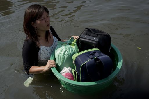 A local resident walks in floodwaters with her suitcases in a plastic bowl as she leaves her home, after a mud and sandbag wall collapsed in Bang Bua Thong, in Nonthaburi province, suburban Bangkok, on October 19, 2011. Thailand's premier urged the kingdom's rival political factions to work together to tackle the worst floods in decades, as the opposition called on her to declare a state of emergency. AFP PHOTO/ Nicolas ASFOURI
