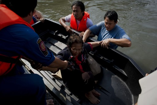 An elderly local resident is evacuated by Thai rescuers in floodwaters, after a mud and sandbag wall collapsed in Bang Bua Thong, in Nonthaburi province, suburban Bangkok, on October 19, 2011. Thailand's premier urged the kingdom's rival political factions to work together to tackle the worst floods in decades, as the opposition called on her to declare a state of emergency. AFP PHOTO/ Nicolas ASFOURI