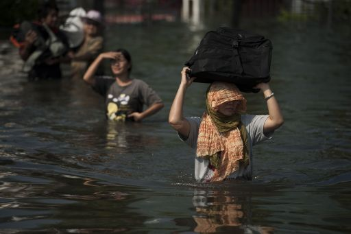 Local residents walk in floodwaters with their suitcases on their heads, as they leave their homes, after a mud and sandbag wall collapsed in Bang Bua Thong, in Nonthaburi province, suburban Bangkok, on October 19, 2011. Thailand's premier urged the kingdom's rival political factions to work together to tackle the worst floods in decades, as the opposition called on her to declare a state of emergency. AFP PHOTO/ Nicolas ASFOURI