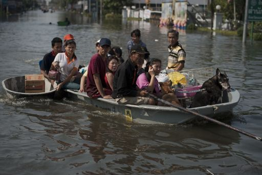 Local residents sit on a boat in floodwaters as they leave their homes with their animals and belongings, after a mud and sandbag wall collapsed in Bang Bua Thong, in Nonthaburi province, suburban Bangkok, on October 19, 2011. Thailand's premier urged the kingdom's rival political factions to work together to tackle the worst floods in decades, as the opposition called on her to declare a state of emergency. AFP PHOTO/ Nicolas ASFOURI