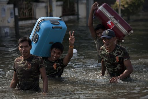 Thai rescuers carry local residents luggage as they walk through floodwaters, after a mud and sandbag wall collapsed in Bang Bua Thong, in Nonthaburi province, suburban Bangkok, on October 19, 2011. Thailand's premier urged the kingdom's rival political factions to work together to tackle the worst floods in decades, as the opposition called on her to declare a state of emergency. AFP PHOTO/ Nicolas ASFOURI