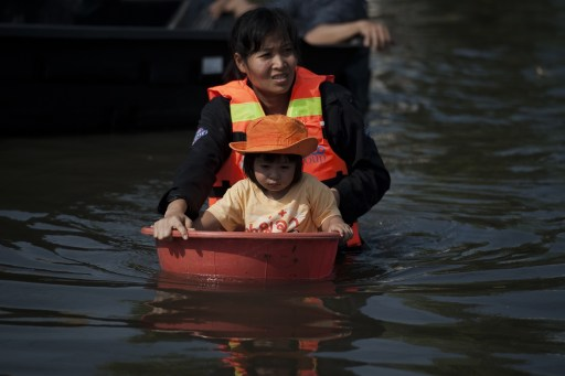 A Thai rescuer holds afloat a girl inside a plastic bowl in floodwaters as water levels rose after a mud and sandbag wall collapsed in Bang Bua Thong in Nonthaburi province, suburban Bangkok, on October 19, 2011. Thailand's premier urged the kingdom's rival political factions on October 19 to work together to tackle the worst floods in decades, as the opposition called on her to declare a state of emergency. AFP PHOTO/ Nicolas ASFOURI