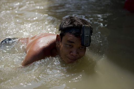 A local resident swims with his mobile phone on his head in floodwaters as water levels rose after a mud and sandbag wall collapsed in Bang Bua Thong in Nonthaburi province, suburban Bangkok, on October 19, 2011. Thailand's premier urged the kingdom's rival political factions on October 19 to work together to tackle the worst floods in decades, as the opposition called on her to declare a state of emergency. AFP PHOTO/ Nicolas ASFOURI