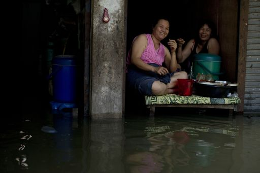 Local residents sit on an elevated wooden furniture in floodwaters as water levels rose after a mud and sandbag wall collapsed in Bang Bua Thong in Nonthaburi province, suburban Bangkok, on October 19, 2011. Thailand's premier urged the kingdom's rival political factions on October 19 to work together to tackle the worst floods in decades, as the opposition called on her to declare a state of emergency. AFP PHOTO/ Nicolas ASFOURI