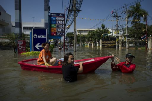 Local residents use a boat as thet navigate through floodwaters as water levels rose after a mud and sandbag wall collapsed in Bang Bua Thong in Nonthaburi province, suburban Bangkok, on October 19, 2011. Thailand's premier urged the kingdom's rival political factions on October 19 to work together to tackle the worst floods in decades, as the opposition called on her to declare a state of emergency. AFP PHOTO/ Nicolas ASFOURI