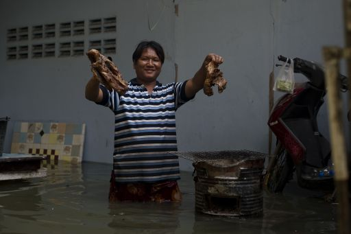 A local resident makes a barbecue in floodwaters as water levels rose after a mud and sandbag wall collapsed in Bang Bua Thong in Nonthaburi province, suburban Bangkok, on October 19, 2011. Thailand's premier urged the kingdom's rival political factions on October 19 to work together to tackle the worst floods in decades, as the opposition called on her to declare a state of emergency. AFP PHOTO/ Nicolas ASFOURI
