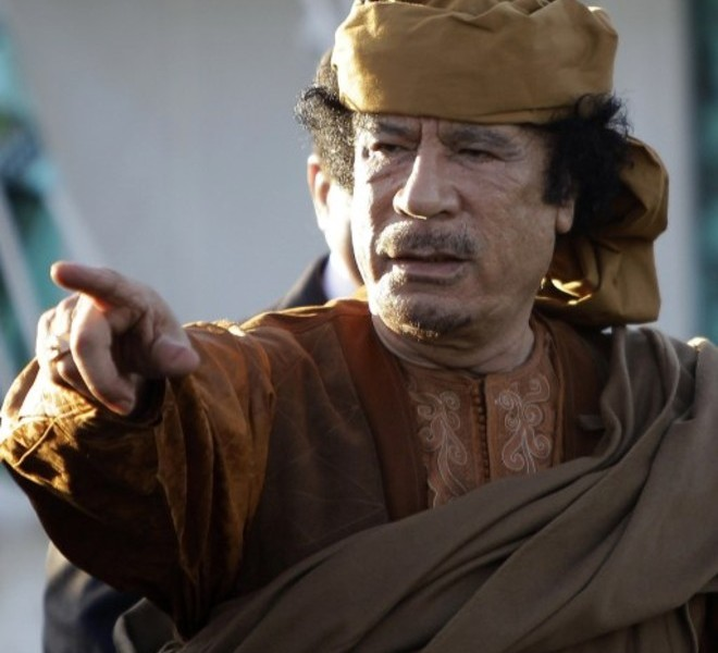 (FILES)  -- A picture taken on April 10, 2011 shows Libyan leader Moamer Kadhafi gesturing outside his tent at his Bab al-Aziziya residence after his meeting with African leaders in Tripoli. Libyan TV quoted a National Transitional Council (NTC) commander as saying Kadhafi was captured in his hometown Sirte on October 20 , 2011.  AFP PHOTO/JOSEPH EID