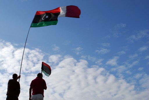 Libyans wave their new national flag (L) and Qatar's flag during a ceremony announcing the liberation for the country in the eastern city of Benghazi on October 23, 2011 three days after ousted despot Moamer Kadhafi was captured and killed. AFP PHOTO/ABDULLAH DOMA