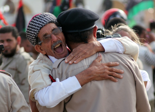 Libyans celebrate following the official of liberation for the country in the eastern city of Benghazi on October 23, 2011 three days after ousted despot Moamer Kadhafi was captured and killed.   TOPSHOTS / AFP PHOTO / ABDULLAH DOMA