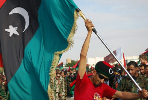 A Libyan man waves his new national flag during a ceremony announcing the liberation for the country in the eastern city of Benghazi on October 23, 2011 three days after ousted despot Moamer Kadhafi was captured and killed. AFP PHOTO/ABDULLAH DOMA