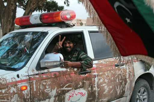 "A Libyan National Transitional Council (NTC) fighter flashes the victory sign as NTC troops arrive in Benghazi from Sirte on October 22, 2011. The eastern Libyan city of Benghazi rocked with gunfire and chants of ""Allahu Akbar"" (God is Great) as trucks full of fighters who defeated Moamer Kadhafi's forces in his hometown of Sirte returned home. AFP PHOTO/ABDULLAH DOMA"