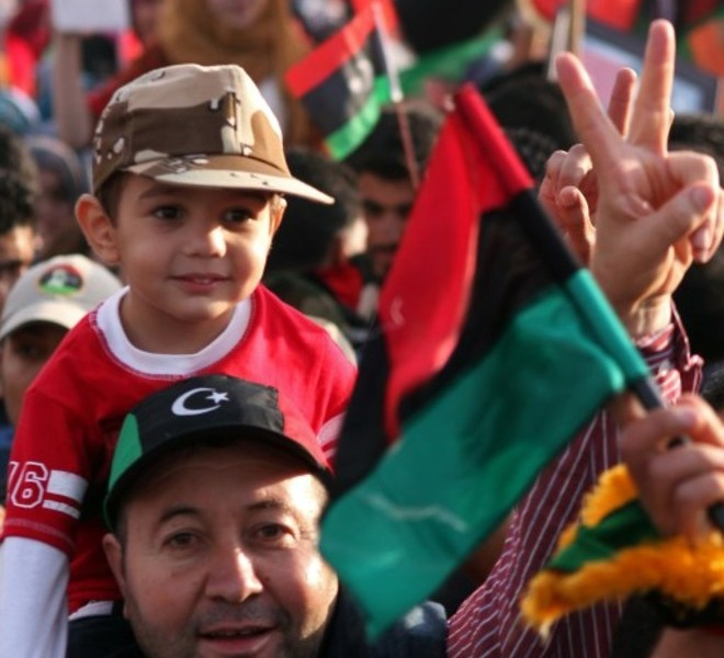 Libyans celebrate during a ceremony announcing the liberation for the country in the eastern city of Benghazi on October 23, 2011 three days after ousted despot Moamer Kadhafi was captured and killed. AFP PHOTO/ABDULLAH DOMA