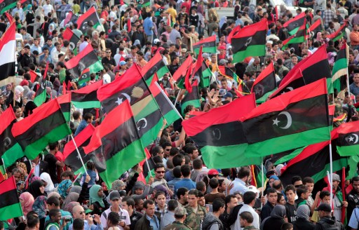 Libyans wave their new national flag as they celebrate following the official of liberation for the country in the eastern city of Benghazi on October 23, 2011 three days after ousted despot Moamer Kadhafi was captured and killed,AFP PHOTO/ABDULLAH DOMA