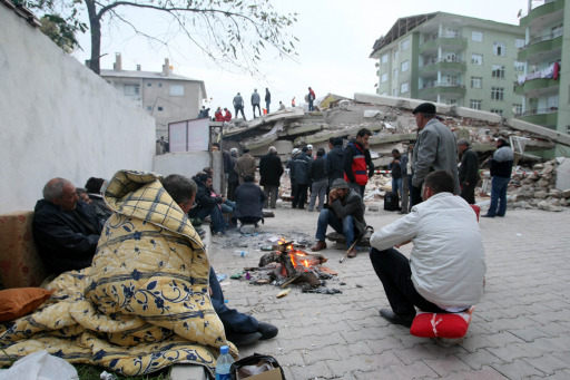 Survivors of the earthquake warm up next to a fire in Ercis, on October 24, 2011.  A total of 970 buildings collapsed as a result of the 7.2-magnitude quake and aftershocks, and some 1,200 rescue officials were frantically scrambling to pull out any survivors before the start of the second night since the quake, with temperatures expected to plunge to two degrees Celsius (36 Fahrenheit) and snow forecast for Wednesday. AFP PHOTO/ADEM ALTAN