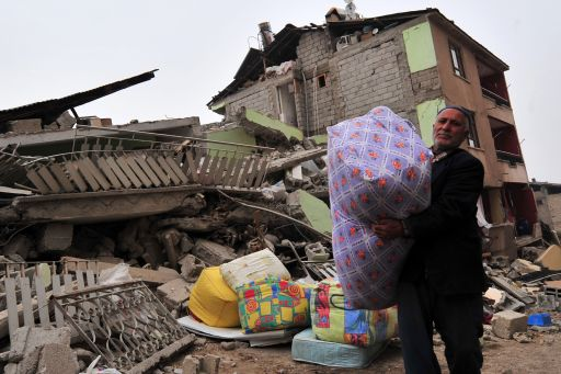 A Turkish man collects his belongs from a collapsed building following an earthquake in Ercis, in the eastern Turkey province of Van, on October 25, 2011. A 7.2-magnitude earthquake that struck eastern Turkey killed 366 people and injured some 1,300, the emergency unit of the prime minister's office said on October 25. More than 2,200 buildings were damaged in the tremor that hit Van province, it added in a statement on its web site. AFP PHOTO/MUSTAFA OZER