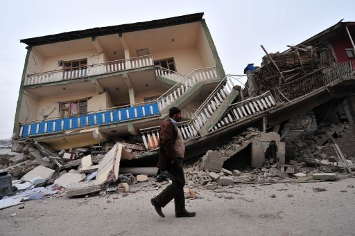 A Turkish man walks past a collapsed building following an earthquake in Ercis, in the eastern Turkey province of Van, on October 25, 2011. A 7.2-magnitude earthquake that struck eastern Turkey killed 366 people and injured some 1,300, the emergency unit of the prime minister's office said on October 25. More than 2,200 buildings were damaged in the tremor that hit Van province, it added in a statement on its web site. AFP PHOTO/MUSTAFA OZER