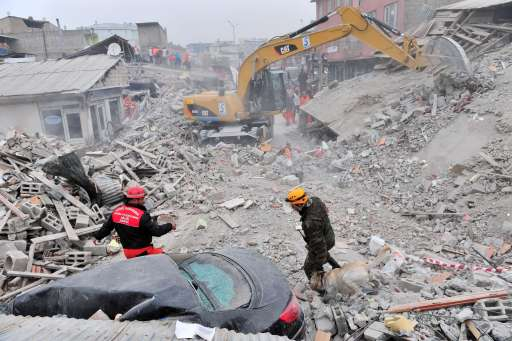 A rescue worker from Azerbaijan takes part with his dog in an operation to salvage people from a collapsed building as a crane is used to dig through rubble following an earthquake in Ercis, in the eastern Turkey province of Van, on October 25, 2011. A 7.2-magnitude earthquake that struck eastern Turkey killed 366 people and injured some 1,300, the emergency unit of the prime minister's office said on October 25. More than 2,200 buildings were damaged in the tremor that hit Van province, it added in a statement on its web site. AFP PHOTO/MUSTAFA OZER