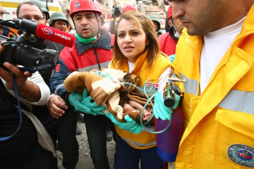 Rescue workers carry Azra Karaduman, a two-week-old baby who was pulled from the debris of the earthquake on October 25, 2011 in Ercis. The mother of the infant was also alive but buried in the wreckage of their home in the town of Ercis and rescuers were trying to reach her. The rescue workers reached the baby, named Azra according to the reports, after hours of frantic digging and were working to free the mother whose name was given as Semiha. The father was missing, rescuers said. AFP PHOTO / ADEM ALTAN