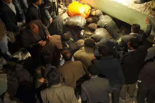 Turkish men retrieve the body of a victim as they take part in a rescue operation to salvage people from a collapsed building after an earthquake in the Ercis province of Van, in eastern Turkey, on October 23, 2011. More than 1,000 people were likely to have been killed in an earthquake as powerful as the one that struck on 23 October in eastern Turkey, experts from the Kandilli Observatory and Earthquake Research Institute said at a press conference broadcast on Turkish TV. AFP PHOTO / MUSTAFA OZER