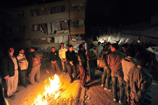 Residents of Ercis stand near a fire on a street, surrounded by collapsed buildings, after an earthquake in the Van province, in eastern Turkey, on October 23, 2011. More than 1,000 people were likely to have been killed in an earthquake as powerful as the one that struck on 23 October in eastern Turkey, experts from the Kandilli Observatory and Earthquake Research Institute said at a press conference broadcast on Turkish TV. AFP PHOTO / MUSTAFA OZER