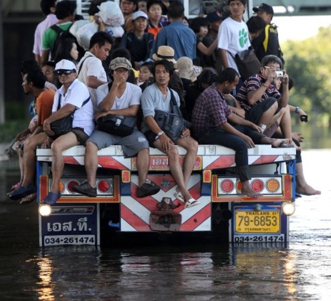 Thai residents are transported on a truck through floodwaters in Bangkok on October 27, 2011. Bangkok residents were fleeing the capital October 27 after authorities called an emergency five-day holiday and urged people in flood-prone parts of the city to leave to avoid a massive deluge. AFP PHOTO / Pornchai KITTIWONGSAKUL
